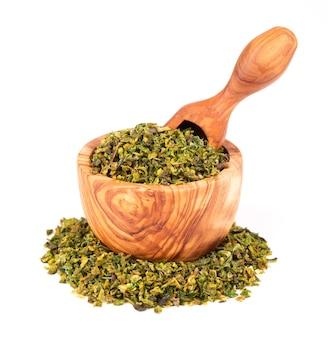 Getrocknete grüne paprikaflocken mit samen in olivenschale und schaufel, isoliert auf weißem hintergrund. gehackte jalapeno, habanero oder chilischote. gewürze und kräuter.
