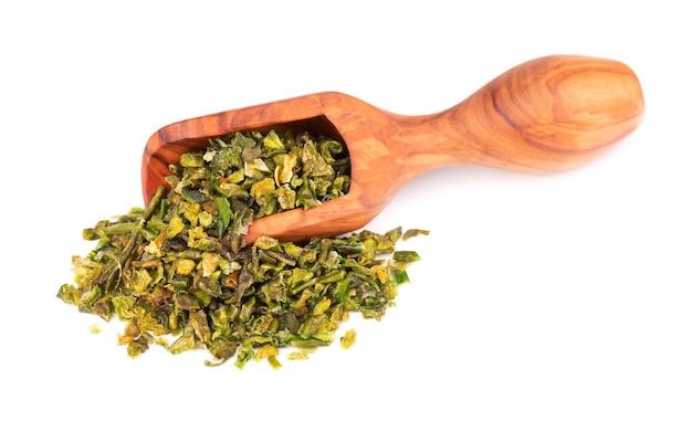 Getrocknete grüne paprikaflocken mit samen in olivenschaufel, isoliert auf weißem hintergrund. gehackte jalapeno, habanero oder chilischote. gewürze und kräuter.