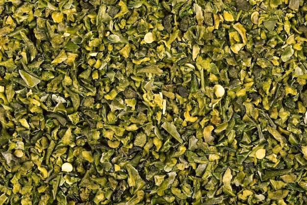 Getrocknete grüne paprikaflocken mit samenhintergrund. gehackte jalapeno, habanero oder chilischote. gewürze und kräuter.