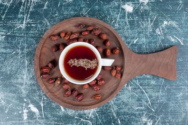 Getrocknete hagebutte und eine tasse tee auf holzbrett.