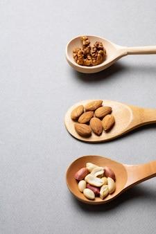 Getrocknete haselnuss, cashew, mandeln in holzlöffeln auf grau.
