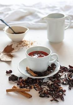 Getrocknete hibiskusblätter für tee oder aufgüsse, zimtstangen und braunen zucker
