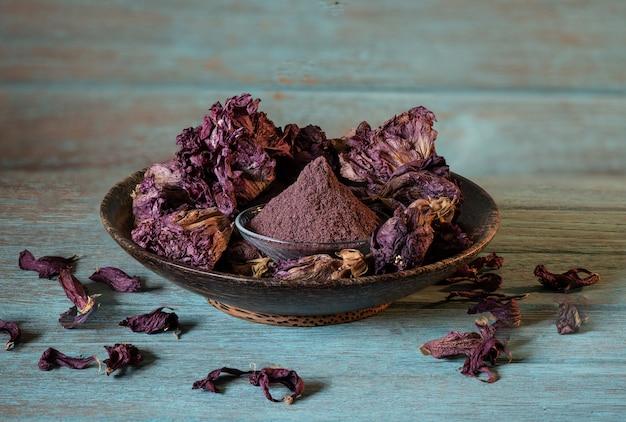 Getrocknete hibiskusblüte und pulver auf einem alten holz.