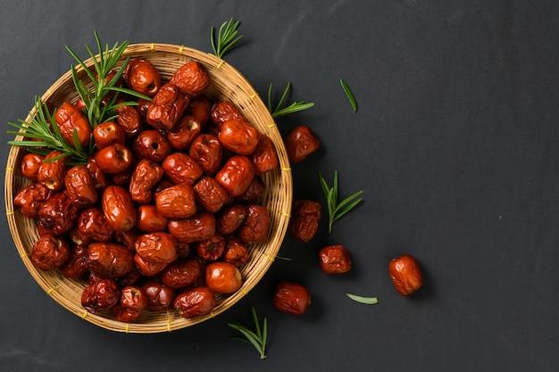 Getrocknete jujube, chinesische getrocknete rote dattelfrucht mit rosmarinblatt im bambuskorb auf schwarzem hintergrund, kräuterfrüchte.