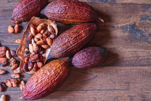 Getrocknete kakaofrucht und getrocknete kakaobohnen auf altem hölzernem hintergrund
