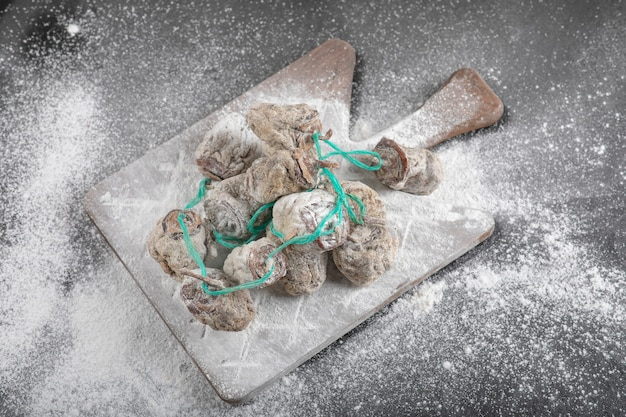Getrocknete kakifrüchte mit mehl dekoriert auf schwarzer oberfläche