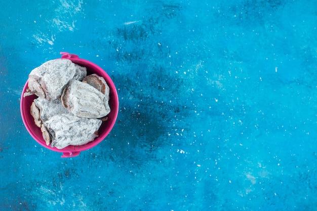 Getrocknete kakis in einem eimer, auf dem blauen tisch.