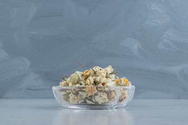 Getrocknete kamillenblüten in glasschale.