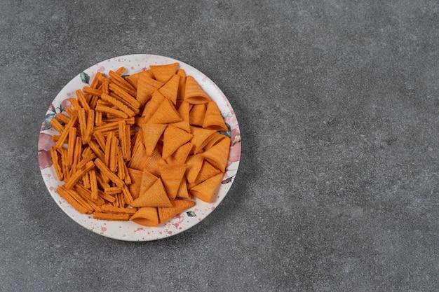 Getrocknete kegelförmige maischips mit brotkäsegeschmack in einer platte auf der marmoroberfläche