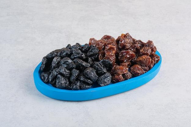 Getrocknete kirschen und pflaumen in einer blauen servierplatte.