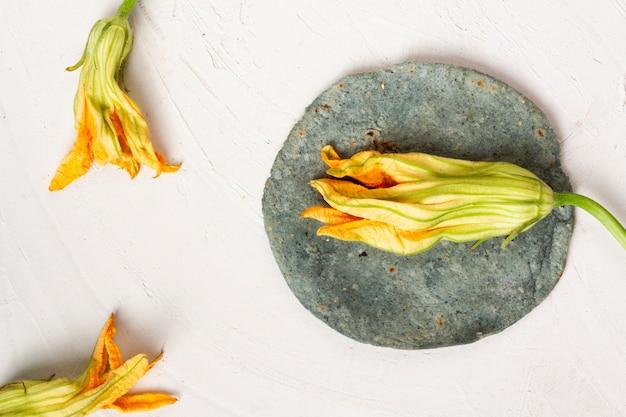 Getrocknete kürbisblume der draufsicht mit spinattortilla