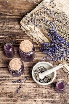Getrocknete lavendelblüten in einem mörser und stößel mit einer flasche ätherischem lavendelöl