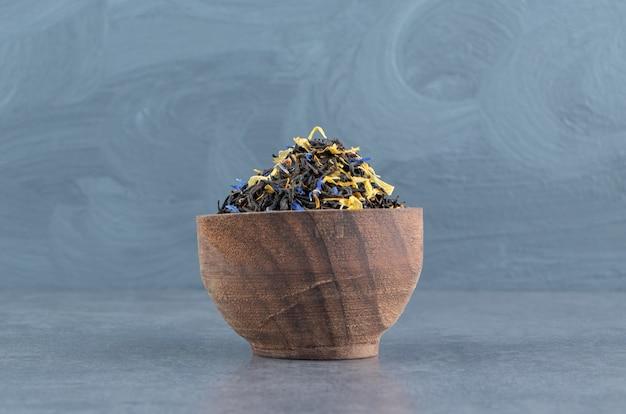 Getrocknete lose tees mit weizen auf einer holzschale