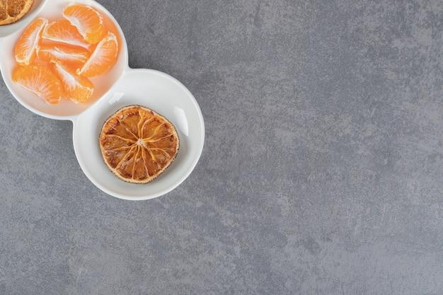 Getrocknete mandarinenscheiben und frische segmente in weißen schalen. foto in hoher qualität