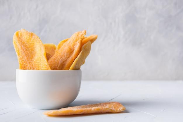 Getrocknete mango-chips auf weiß. nahansicht.