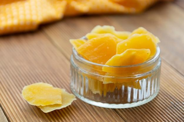 Getrocknete mango in der glasschüssel auf hölzernem hintergrund