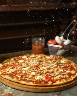 Getrocknete minzblätter werden über hühnerpizza gestreut
