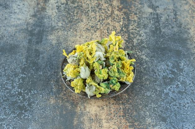 Getrocknete natürliche gelbe blumen in metallschale.