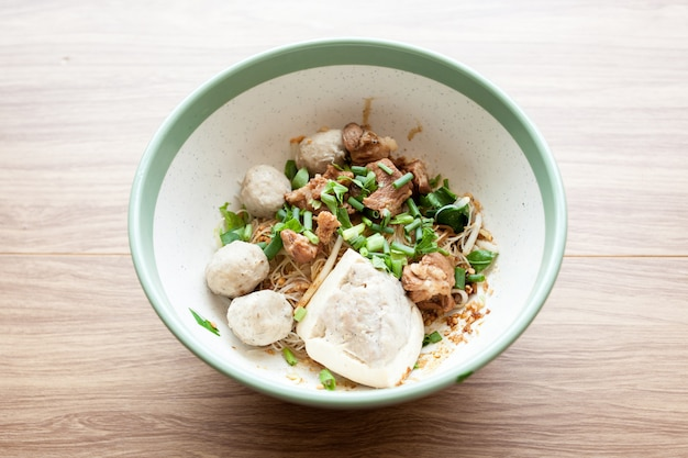 Getrocknete nudel mit tofu-schweinefleisch, fleischbällchen und gekochtem schweinefleisch in der großen schüssel setzen auf hölzernen hintergrund