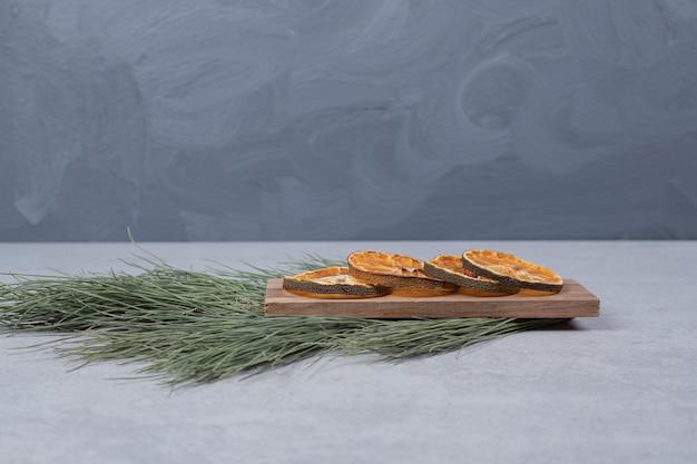 Getrocknete orange auf holzbrett mit zweig des grünen baumes. hochwertiges foto