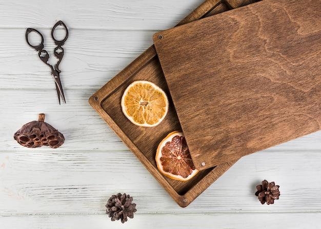 Getrocknete orange; grapefruitscheibe; lotus-hülse; tannenzapfen mit einer schere auf einem weißen holztisch