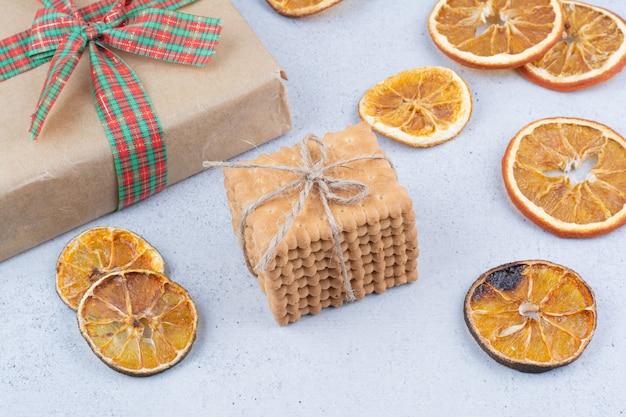 Getrocknete orange, kekse und geschenkbox auf marmorhintergrund.