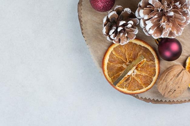 Getrocknete orange mit tannenzapfen und weihnachtskugeln auf holzteller. hochwertiges foto