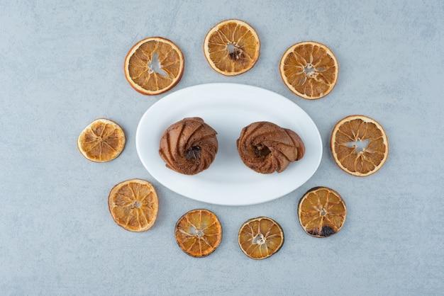 Getrocknete orange mit zwei köstlichen cupcakes auf weißem hintergrund