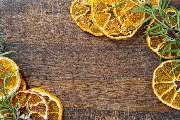 Getrocknete orangen mit basilikum-blätter-rahmen. getrocknete zitrusfrüchte auf hölzerner hintergrundrahmenschablone. platz kopieren.