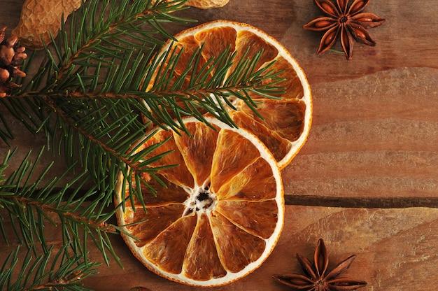 Getrocknete orangen und tannenbaumast auf rustikaler holzoberfläche