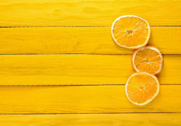 Getrocknete orangenscheiben auf einem gelben holztisch. fruchtkonzept. trend des minimalismus. draufsicht.
