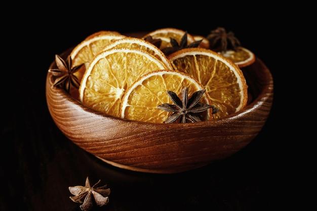 Getrocknete orangenscheiben in einem holzteller.
