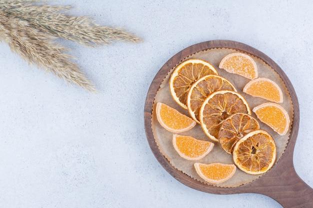 Getrocknete orangenscheiben und marmeladen auf holzbrett.