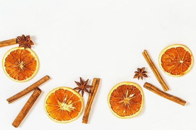 Getrocknete orangenscheiben und zimtstangen. gewürze für heißen wein.