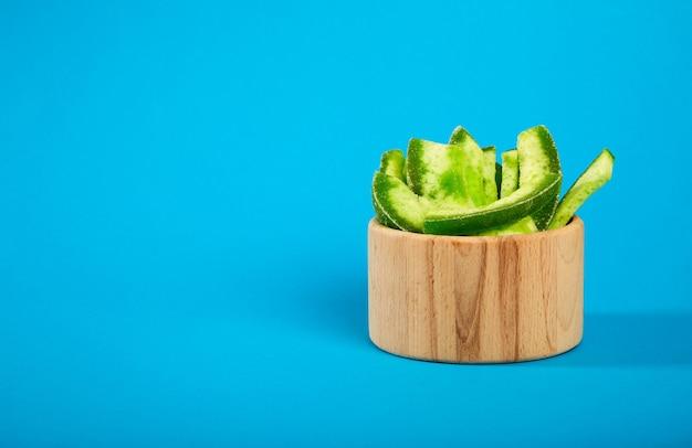 Getrocknete pampelmusenfrüchte in einer holzschale auf blau