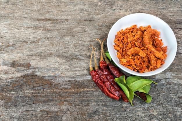 Getrocknete paprikas und gebratene schweinefleischgewürze, getrocknete paprikas zum essen zusammen mit thailändischem essen.
