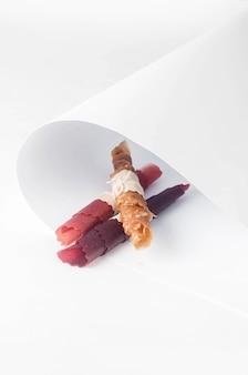 Getrocknete pastille - fruchtleder rollt süßigkeiten auf abstraktem weißem hintergrund. fruchtchips. gesundes ernährungskonzept, snack, kein zucker. ansicht von oben, kopienraum.
