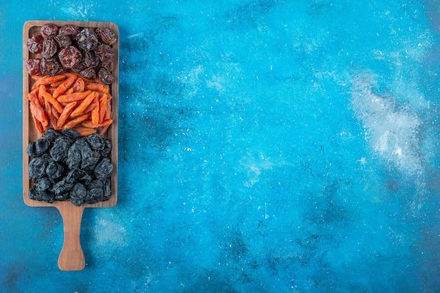 Getrocknete pflaumen und aprikosen auf einem brett, auf dem blauen tisch.