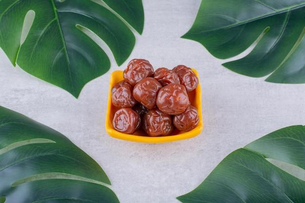 Getrocknete pflaumenkirschen in einer tasse auf konkretem hintergrund. foto in hoher qualität
