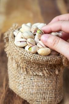 Getrocknete pistazien im kleinen sack. getreide für gesundes. gutes fett.