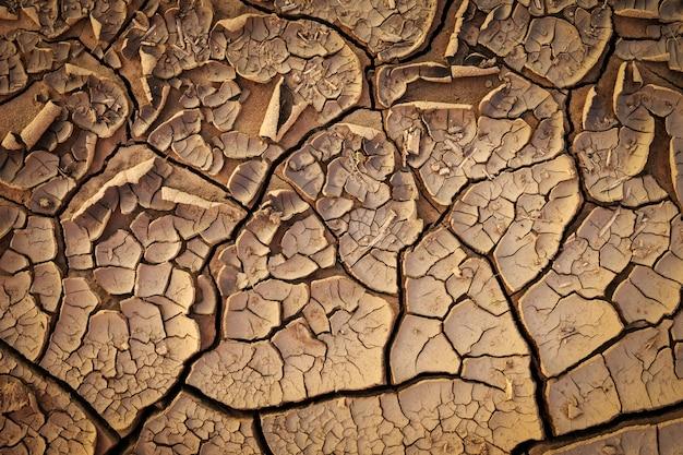 Getrocknete rissige erdboden-bodentextur.
