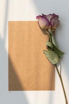 Getrocknete rosa rose mit einer braunen karte