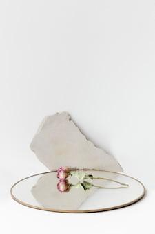 Getrocknete rose auf einem runden spiegel