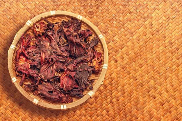Getrocknete rosellenblume in der holzschale auf braunem gewebtem schilfmattenhintergrund für gemachten kräutertee oder rosellasaft