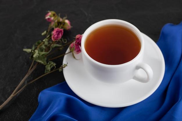 Getrocknete rosen mit einer tasse heißem tee auf einem schwarzen tisch.