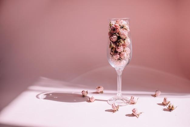 Getrocknete rosenblüten in einem weinglas in der sonne auf einem rosa