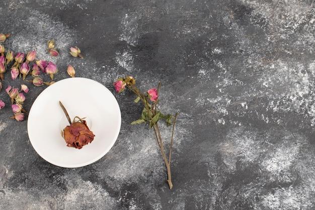 Getrocknete rosenknospen auf einem steintisch.
