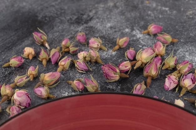 Getrocknete rosenknospen auf steinhintergrund gelegt.