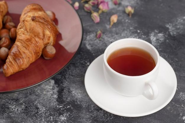 Getrocknete rosenknospen mit einer tasse heißen tees auf einem steintisch.