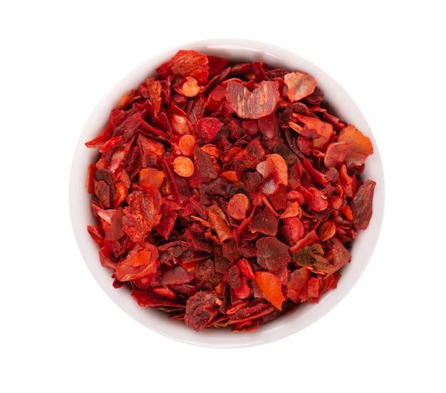 Getrocknete rote chiliflocken in der schüssel, isoliert auf weißem hintergrund. gehackte chili-cayenne-pfeffer. gewürze und kräuter. ansicht von oben.